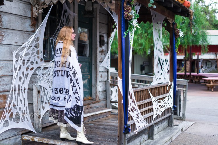 Myself, standing on the porch of a distressed old west wood building, faux cobwebs hang around the edge, wearing a long, black, white, and grey dress, with a black velvet bodice, and billowy white sleeves. A shawl, featuring the design of a Ouija board is printed on the shawl.