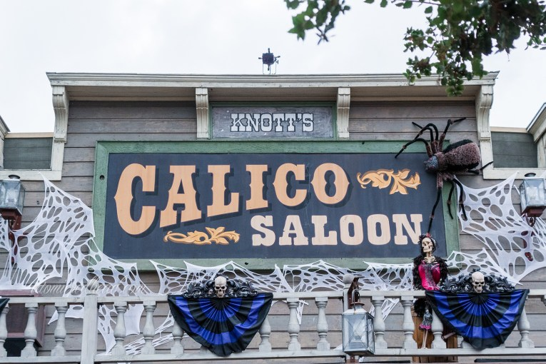 "The Calico Saloon, a two story old west building covered in faux cobwebs, a giant spider looms over the sign reading ""Calico Saloon"" and a skeleton in a red can-can girl dress stands at the railing of the balcony."