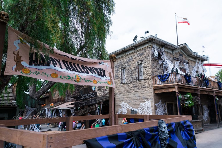"A banner reading ""Happy Halloween"" with jack-o-lanterns hangs on a small stage of Ghost Town. The two story Gold Trails Hotel stands in the background, covered in cobwebs and skeletons stand on the balcony."