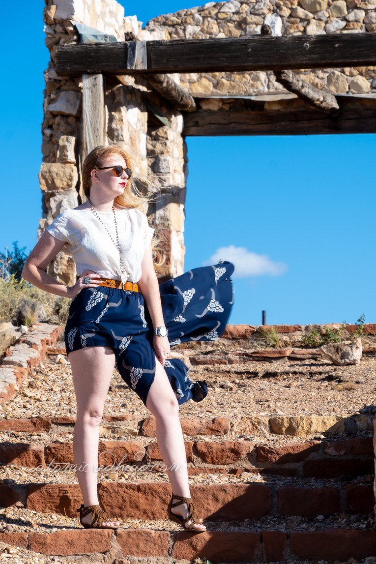 Myself, wearing a white peasant top, and a long, navy skirt with cattle skulls printed on it, and a necklace featuring a cattle skull, walking down the steps of the backside of the stone Mountain Lion structure.