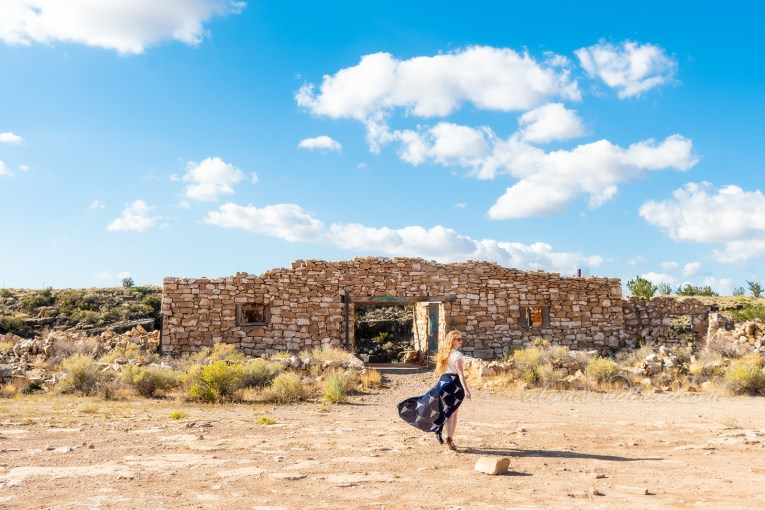 Myself, wearing a white peasant top, and a long, navy skirt with cattle skulls printed on it, and a necklace featuring a cattle skull, walking toward one of the pale tan rock work ruins.