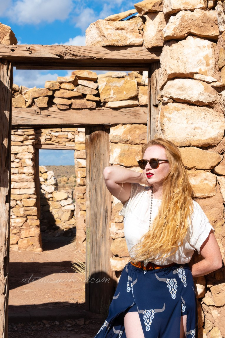 Myself, wearing a white peasant top, and a long, navy skirt with cattle skulls printed on it, and a necklace featuring a cattle skull leaning against a doorway within one of the stone ruins of Tow Guns.