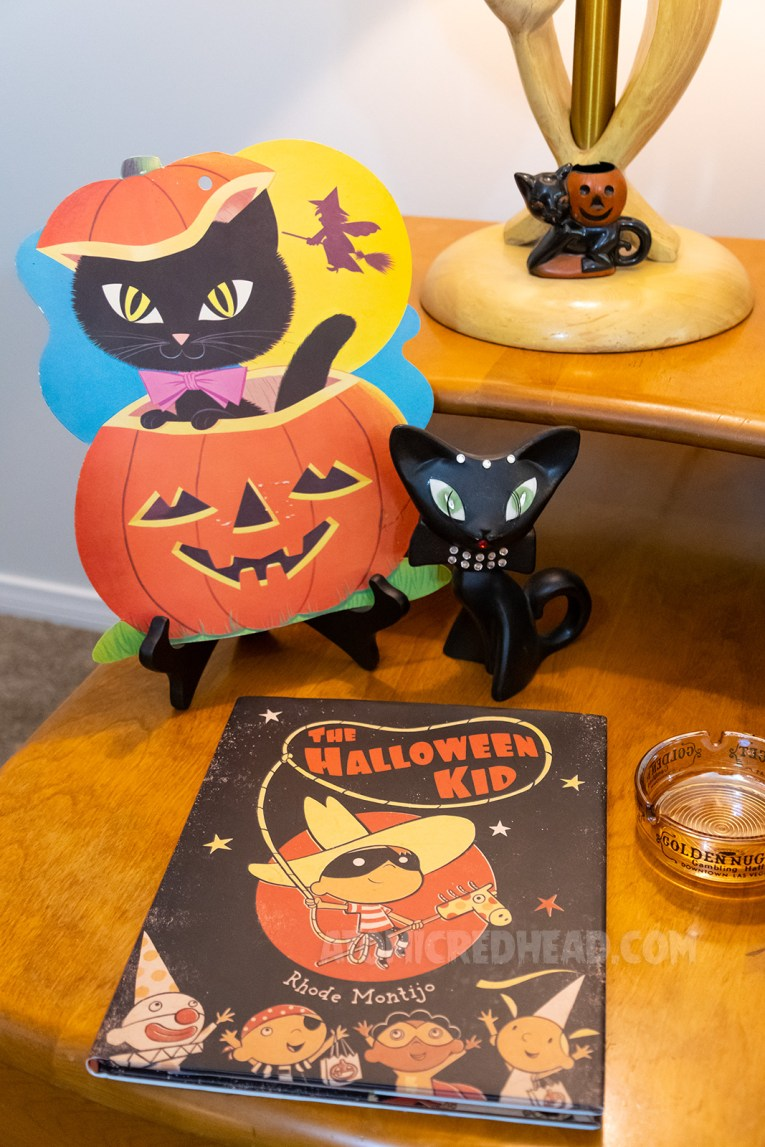 A paper decoration of a black cat peeking out of a jack-o-lantern. Next to it sits a ceramic black cat, and next to it a plastic black cat with a jack-o-lantern.