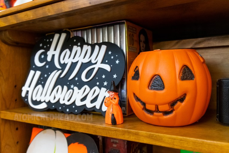 "A black and white sign with a moon and stars reads ""Happy Halloween"" in white script. Next to it is a small orange plastic witch, next to it, a plastic jack-o-lantern."