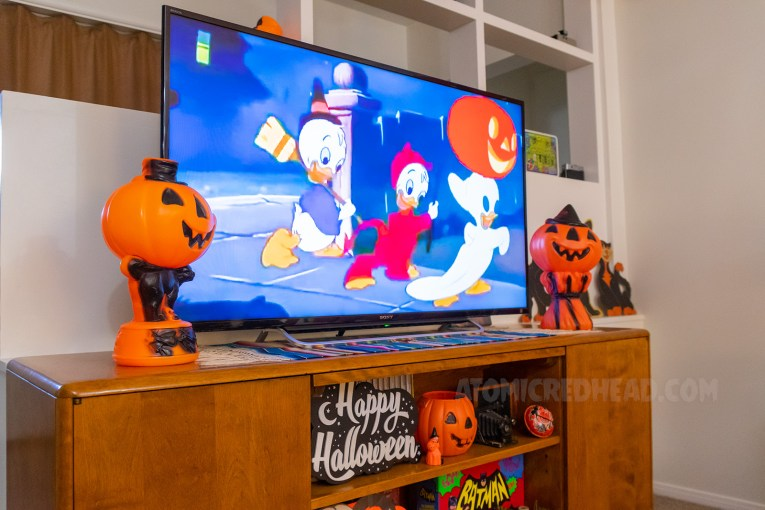 On the TV Donald Duck's nephews dressed as a witch, devil, and ghost, go trick or treating. Flanking the TV are orange plastic jack-o-lanterns.