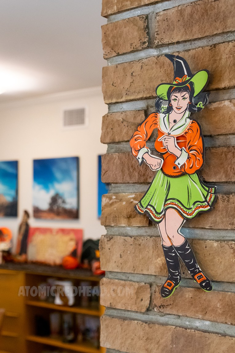 A paper decoration of a young witch wearing an orange and green outfit.
