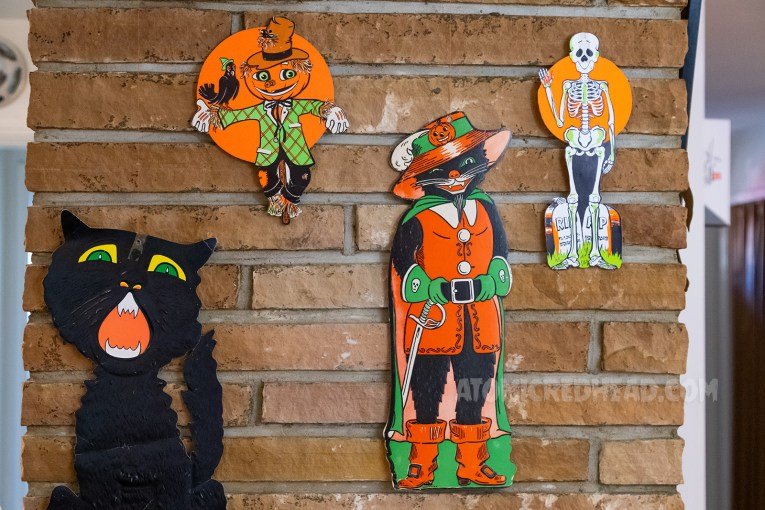 Various paper Halloween decorations hang on the bring fireplace, including a large black cat, a scarecrow, a black cat dressed like a pirate, and a skeleton.