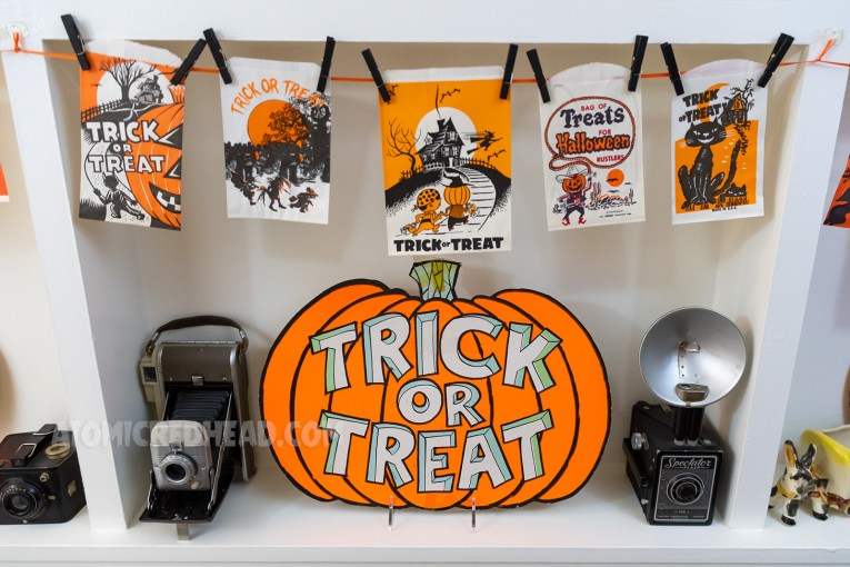 "A paper pumpkin looks like it is carved with ""Trick or Treat"" above it, clothes pinned to ribbon are various small trick or treat bags."