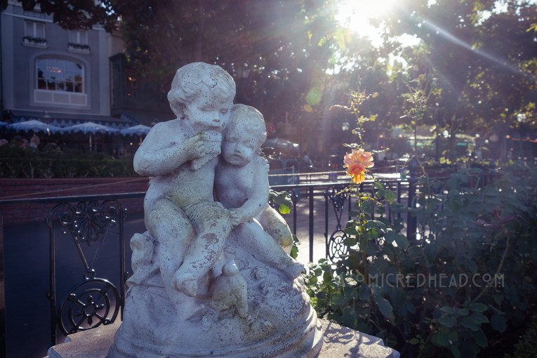 A statue of two cherubs sit among roses.