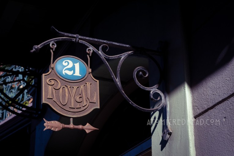 """A metal sign reads """"21 Royal"""" and an arrow points the way."""