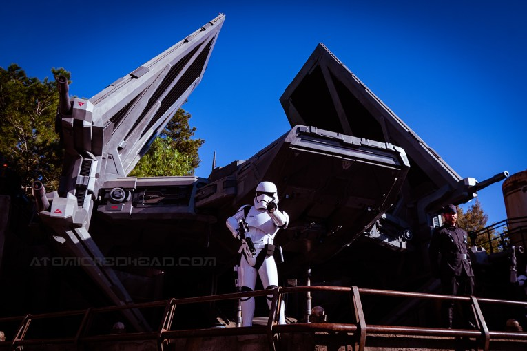 A white stormtrooper stands near a TIE fighter and points at the camera.
