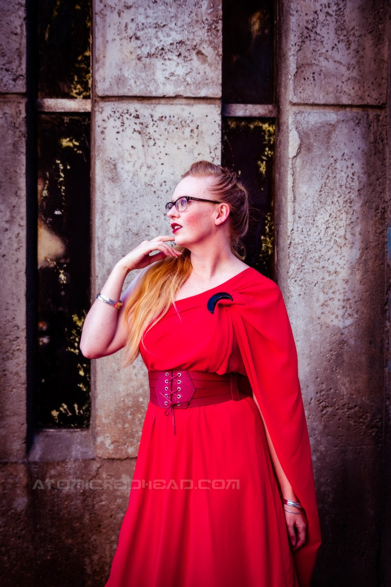 Myself wearing a full length red gown, it is asymmetrical with one shoulder ending in a short cape. A corset style belt at my waist, and a black crescent moon brooch at the shoulder.