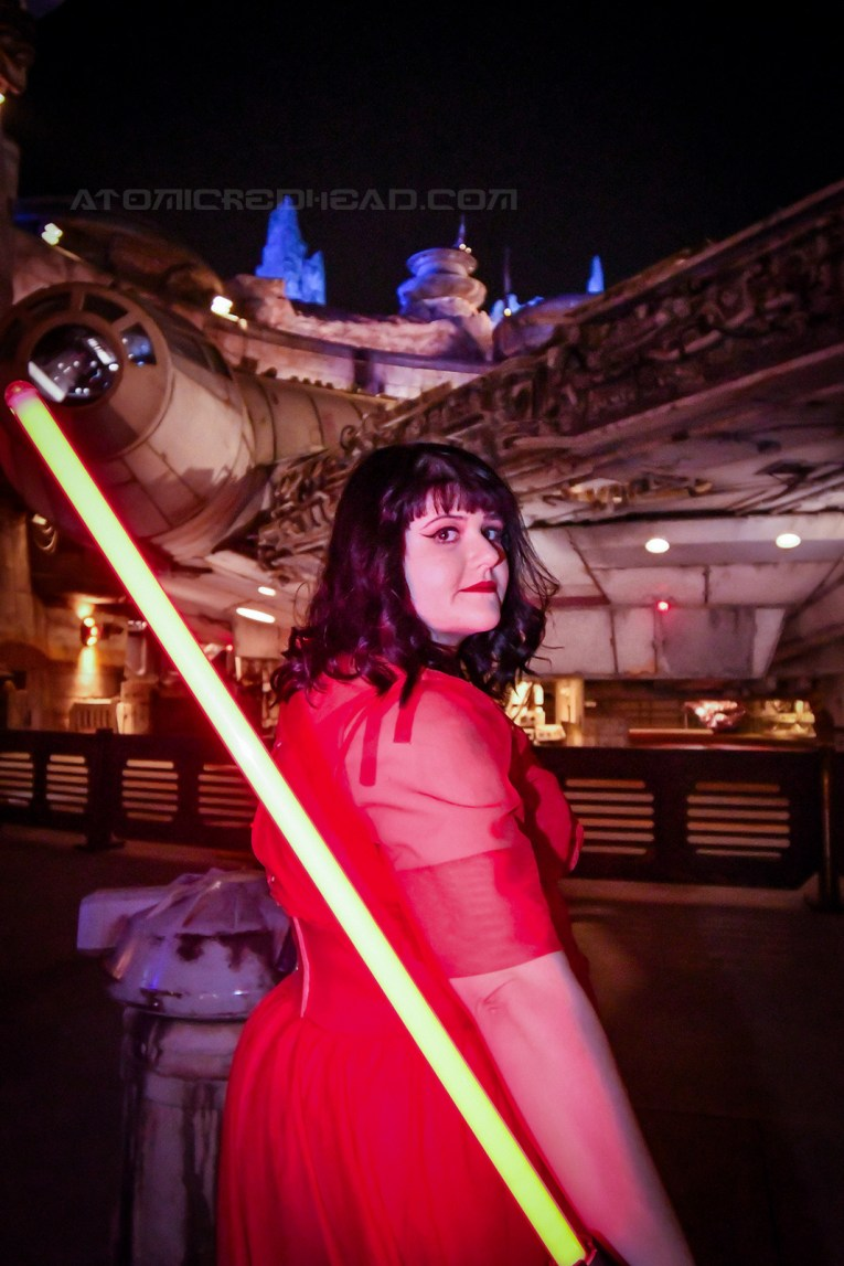 Brittany holds a red light saber near the Falcon.