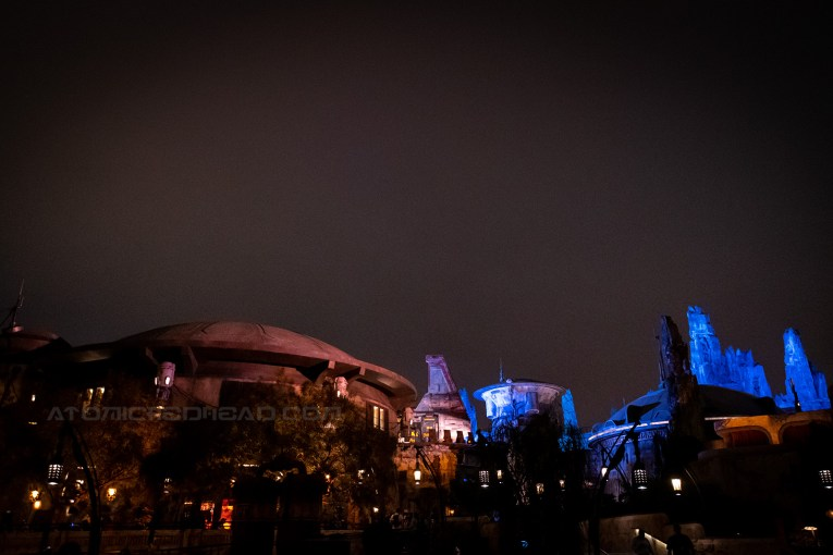 Star Wars: Galaxy's Edge features rounded buildings with dome roofs, lit up with blue and yellow lights at night.