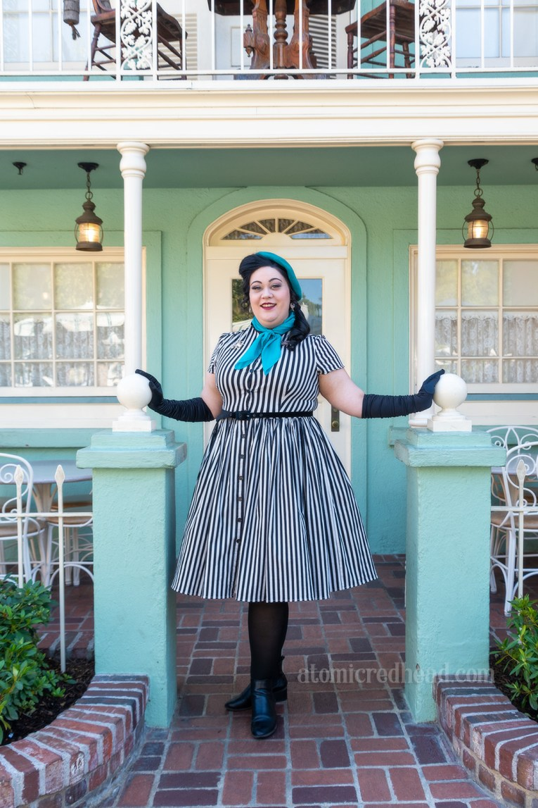 My friend Melissa stands in front of a seafoam colored building with white trim. Melissa wears a black and white stripe shirtwaist dress with a teal beret and scarf, and long black gloves.