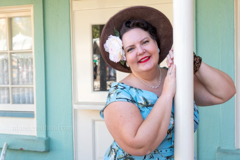 My friend Dor stands in front of a seafoam colored building with white trim. Dor wears a blue dress with a palm tree print. She wears a tan wide brim straw hat and a white flower in her hair.