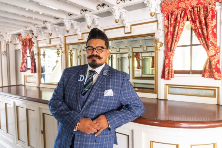 My friend Daniel stands in a cabin aboard the Mark Twain. Daniel wears a blue three-piece suit with a small plaid pattern.