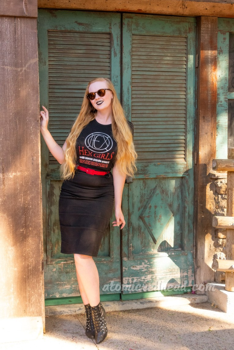 "Myself, standing in front of a green painted wooden door, wearing a black t-shirt with a circular design reading ""HEX"" in the middle. Text below reads ""Hex Girls Spell Bound World Tour 99"" with various cities listed below, a black pencil skirt, with a red belt, and black boots."
