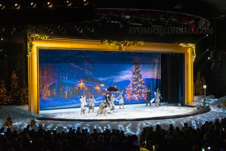 Ice skaters in 1940s outfits skate around the ice rink stage. A backdrop features a small town and tall Christmas tree.