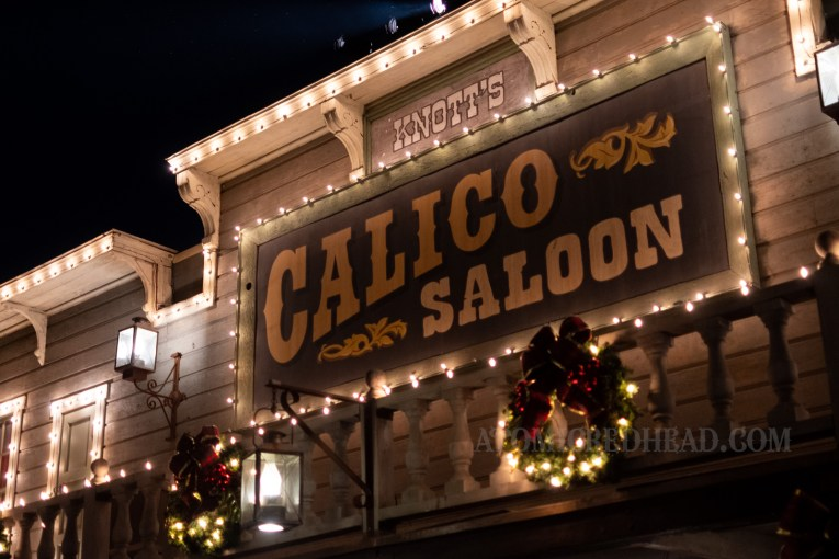 The sign for the Calico Saloon, all lit up with white lights.