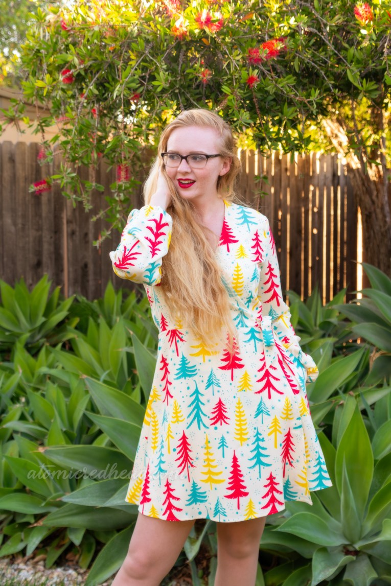 Myself, wearing an off-white short dress with yellow, red, and teal Christmas trees printed on it.