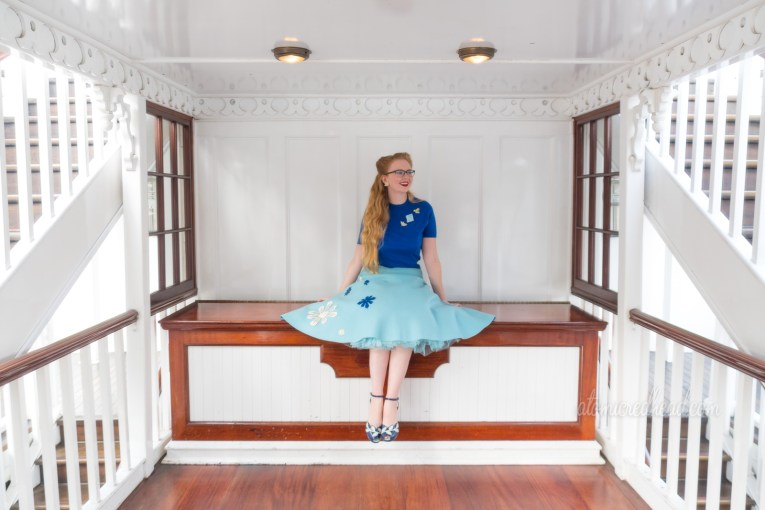 Myself, sitting aboard the Mark Twain, a white paddle wheeler, wearing a bright blue sweater, and a light blue skirt with white and dark blue snowflakes sewn on.