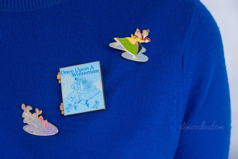 "Close-up of my pins. Top right is a couple in 1860s attire ice skating, the next pin is shaped like a book and reads ""Once Upon a Wintertime"" and features the same couple ice skating, the third pin is a pair of bunnies ice skating."