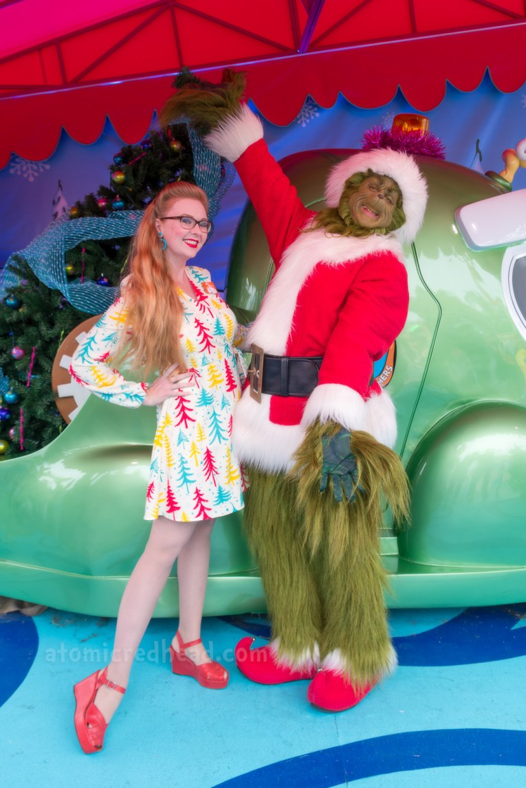 Myself, wearing a cream dress with teal, yellow, and red pine trees printed on it, meeting the Grinch, who is covered in green fur and wears a Santa suit.