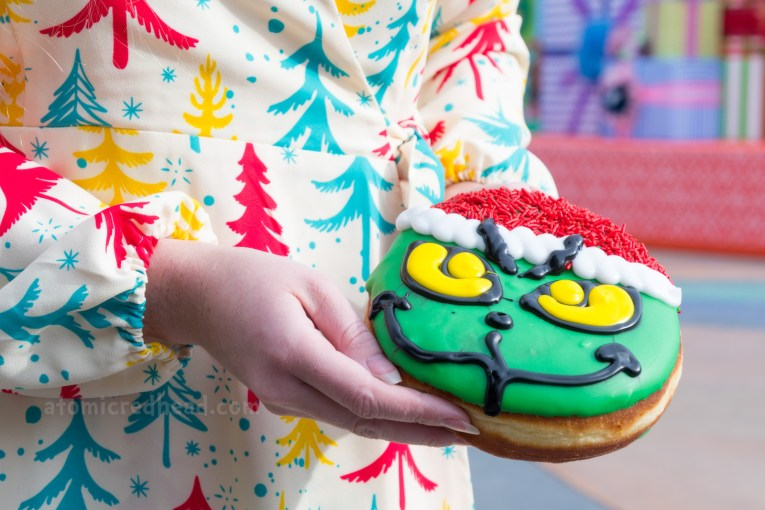 A giant donut of the Grinch with a Santa hat on.