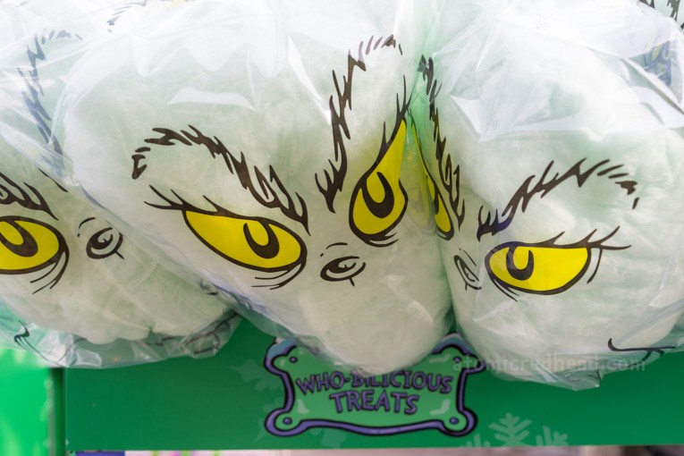 Green cotton candy is wrapped in clear plastic with Grinch eyes and eyebrows printed on it.