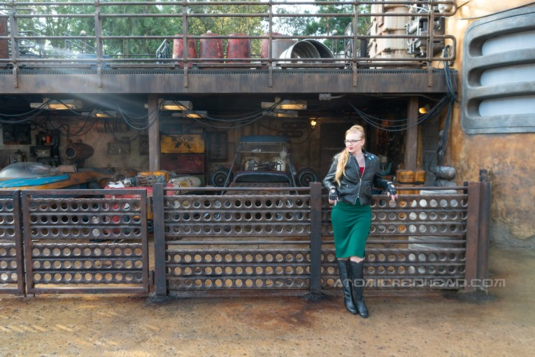 Myself, wearing a black leather jacket, with blue sabacc dice on the upper left, a red peasant top, green pencil skirt, black leather driving gloves, and black knee high leather boots, leaning against a fence in front of various speeders.