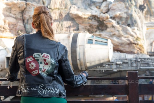 """Myself looking at the Millennium Falcon, the back of my jacket visible, which features red, green, and white cards with symbols on them, and text reading """"Fair and Square"""" along the bottom."""