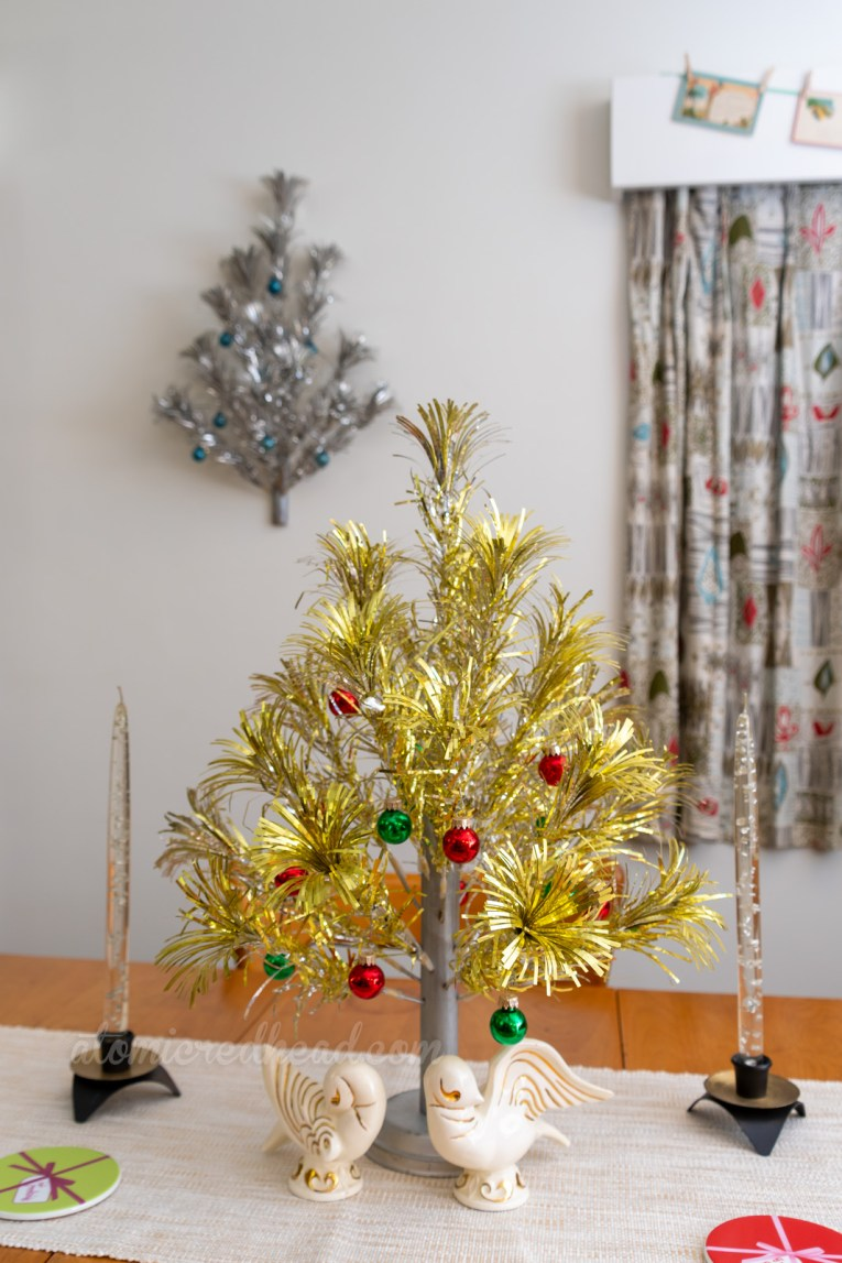 A gold aluminum tree with small red and green balls sits on our dining room table. White ceramic doves sit below. A silver aluminum tree hangs on the wall behind with small blue ornaments.