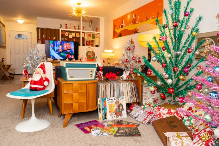 Our living room is divided by our couch and a piece that holds our record player and records. It sits near the aluminum trees, Christmas records scatter the floor.