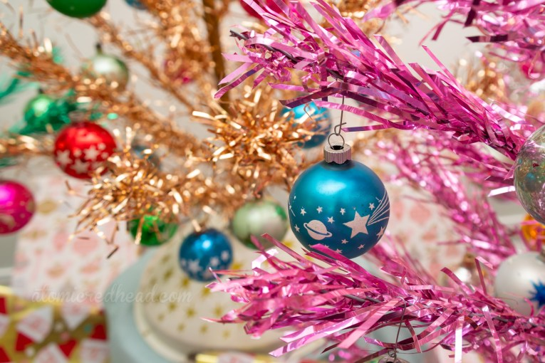 Close-up of a blue ornament with a white design of Saturn and a shooting star, hangs from our pink aluminum tree.