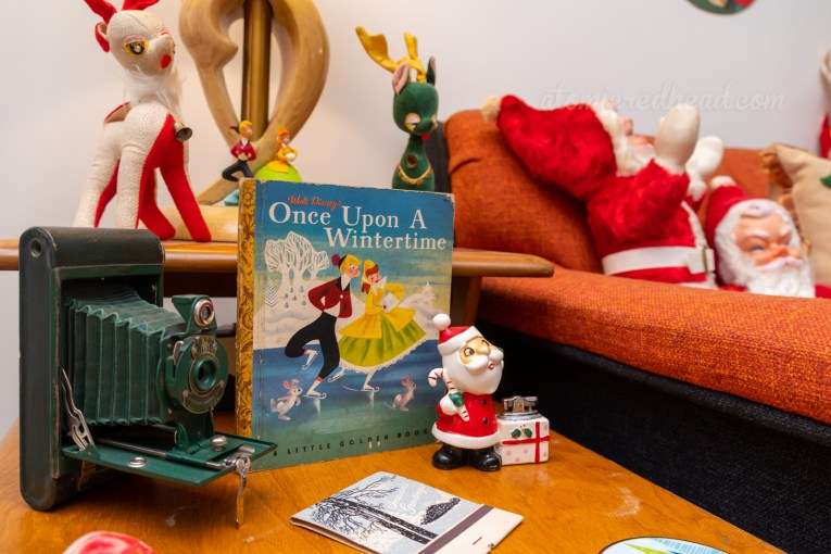 "Close-up of a Little Golden Book for ""Once Upon a Wintertime"" the cover features a couple ice skating. A ceramic figural Santa lighter sits near it."
