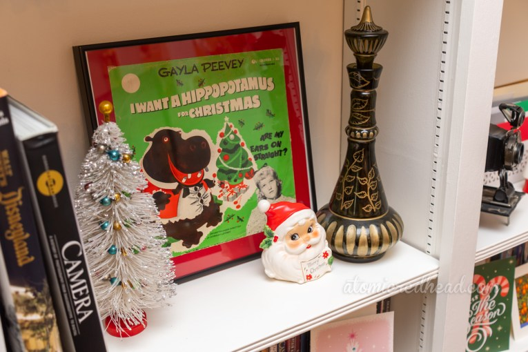 "Close-up of a framed record sleeve for ""I Want a Hippopotamus for Christmas"" and a ceramic Santa letter holder, and a replica of the Jeannie bottle from I Dream of Jeannie."