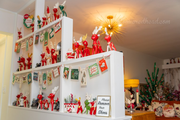A built in room divider between the hall and the living room features vintage Christmas cards stung up like clothes on a line, and small stuffed reindeer.