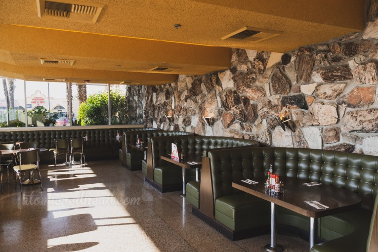 Olive green semicircle booths sit against a rock wall.