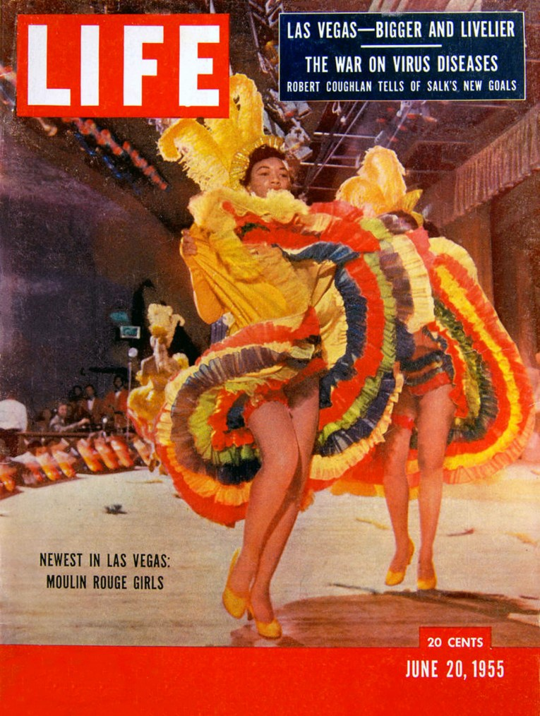 African-American can can dancers in colorful costume dance on the cover of Life Magazine.