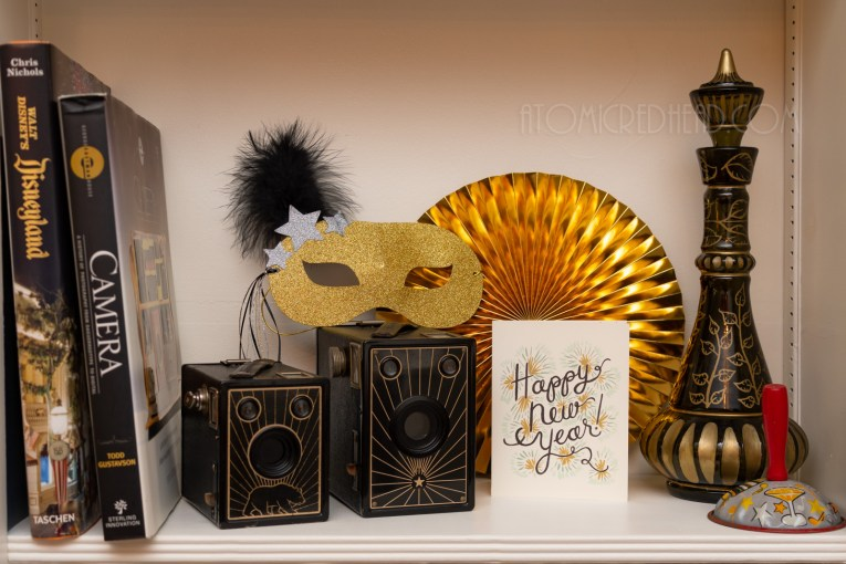 "A gold glitter mask sits on top of two black and gold cameras, a card reading ""Happy New Year"" sits next to the cameras."