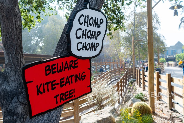"Two signs attached to the trunk of a tree. One reads ""Beware Kite-Eating Tree"" the other is a speech bubble reading ""Chomp Chomp Chomp"""