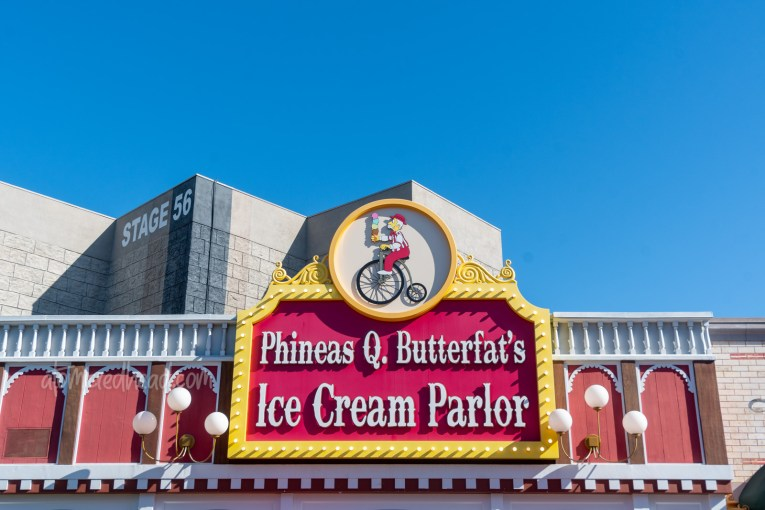 Facade for Phineas Q. Butterfat's Ice Cream Parlor, which is red and white, and features a person on a penny farthing bicycle.