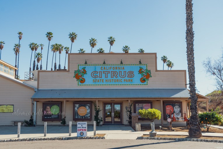 "The Visitor Center, a small cream building that emulates an old citrus packing house. A blue sign flanked by images of oranges reads ""California Citrus State Park"""