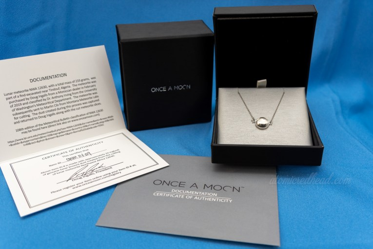 Once a Moon necklace in packaging. A small circular moon line pendant flanked by two small silver stars sits in a silver and black box. Documentation regarding the origins of the lunar dust within the necklace sits next to it.