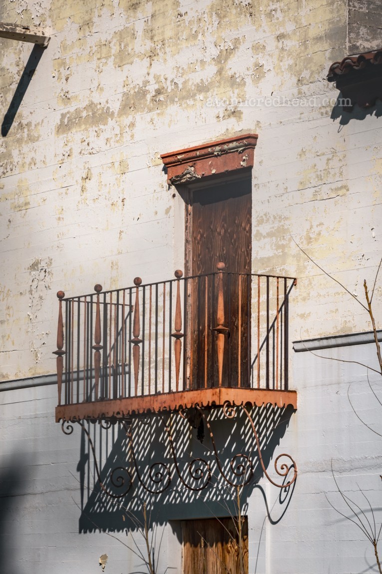 A small metal balcony sits off of a white washed Spanish Revival style building.
