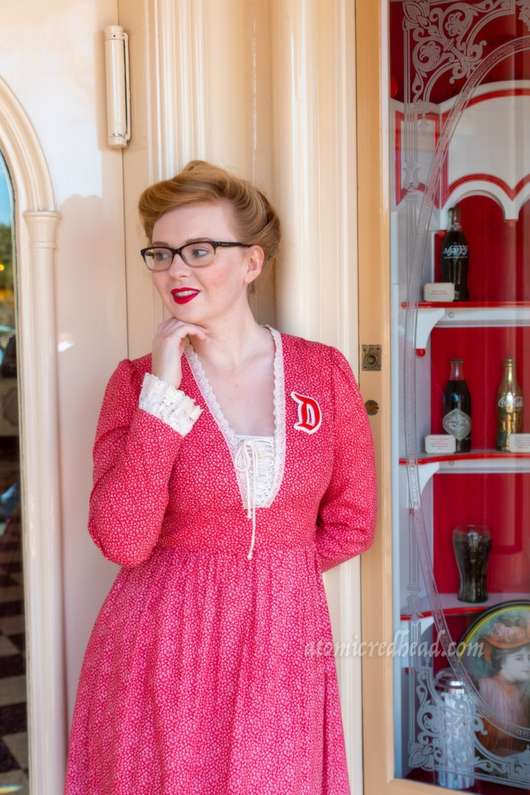"Myself standing in the doorway of a shop on Main Street, wearing a long, red dress with a small floral pattern, with lace trim at the laced V-neckline, and cuffs. A red ""D"" brooch edged in white is worn on my left shoulder, my hair in a Gibson Girl updo."