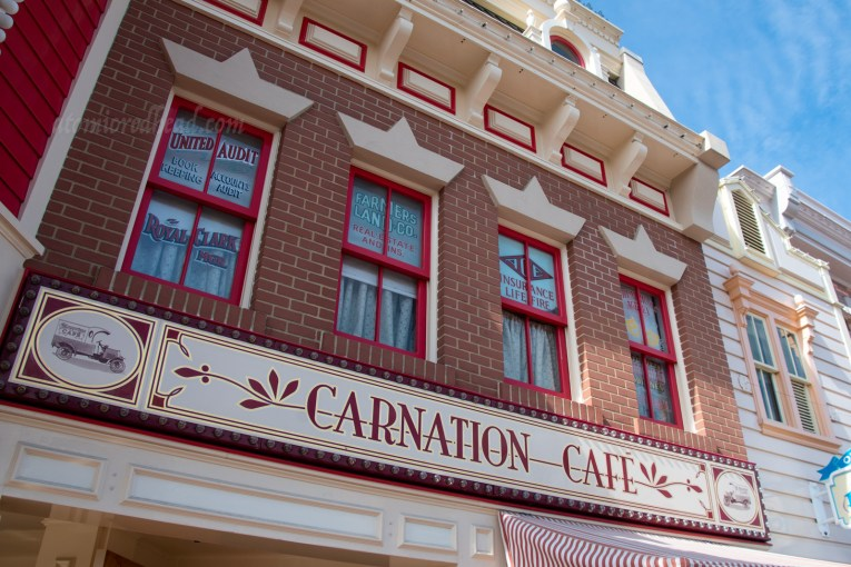 "Sign for the Carnation Cafe, a red building with white trim. A white sign reads ""Carnation Cafe"""
