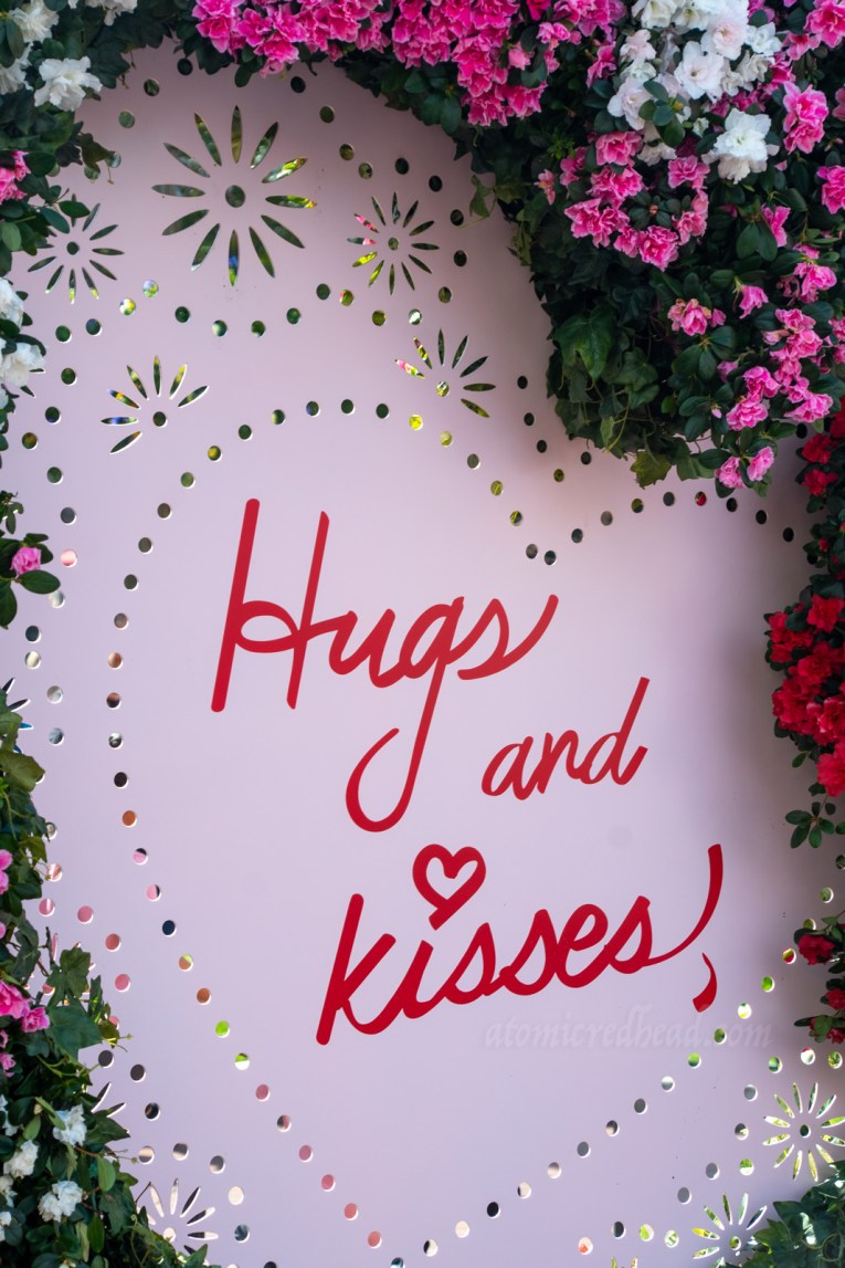"A large pink Valentine sits in the middle of the Town Square, and is edged in pink and white flowers. Script inside reads ""Hugs and Kisses"""