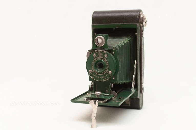 Kodak Rainbow Hawkeye Number 2. A medium sized camera with a bellows, it is dark green in color.